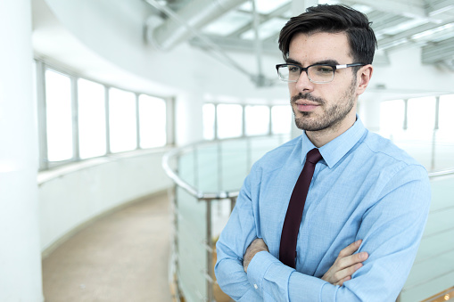 825082848 istock photo Businessman standing arms crossed in office 1024096068