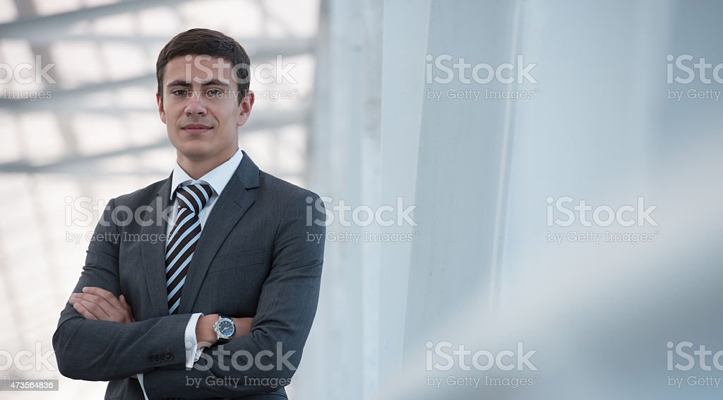 Businessman standing arms crossed stock photo