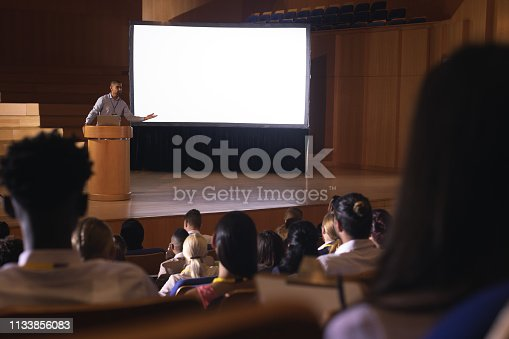 1133973551 istock photo Businessman standing around podium and giving presentation in the auditorium 1133856083