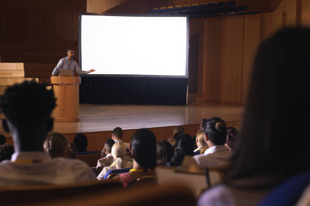 Businessman standing around podium and giving presentation in the auditorium Front view of mixed race businessman standing around podium and giving presentation in the auditorium overhead projector stock pictures, royalty-free photos & images