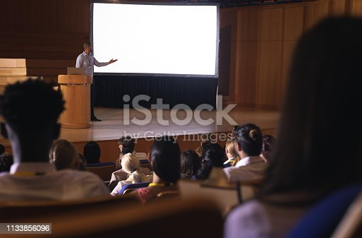 1133973551 istock photo Businessman standing around podium and giving presentation in the auditorium 1133856096