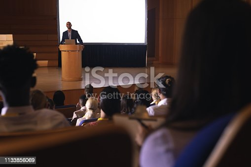 1133973551 istock photo Businessman standing around the podium and giving speech in front of audience in the auditorium 1133856069