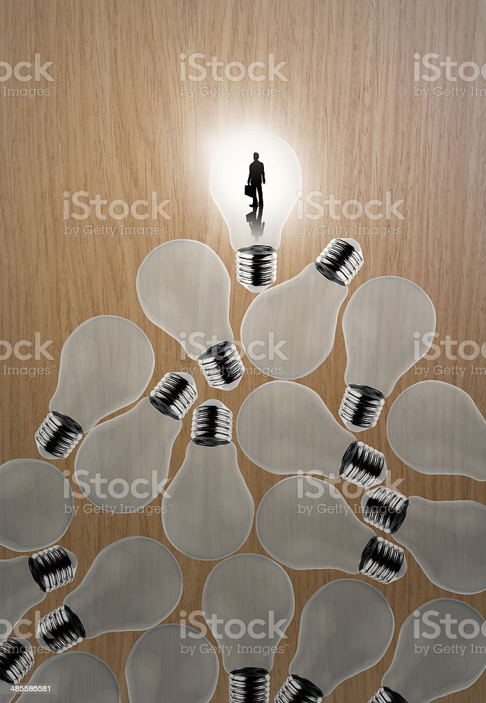 businessman standing at 3d growing light bulb standing out from royalty-free stock photo