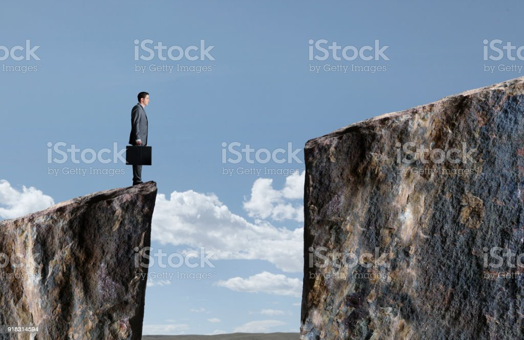 Businessman Standing At Edge Of Cliff stock photo
