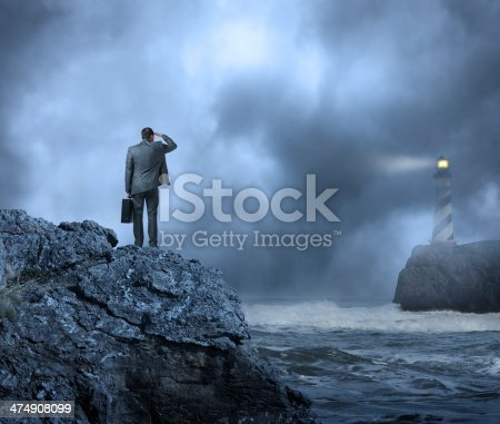 Businessman standing on cliff looking out toward the Beacon of the Lighthouse. Searching for answers.