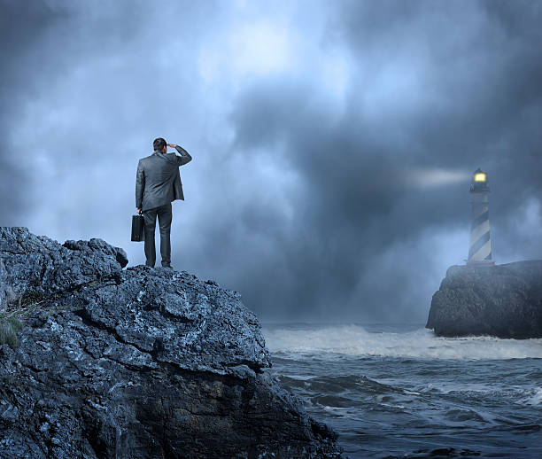 Businessman standing at edge of water looking towards a lighthouse Businessman standing on cliff looking out toward the Beacon of the Lighthouse. Searching for answers. beacon stock pictures, royalty-free photos & images