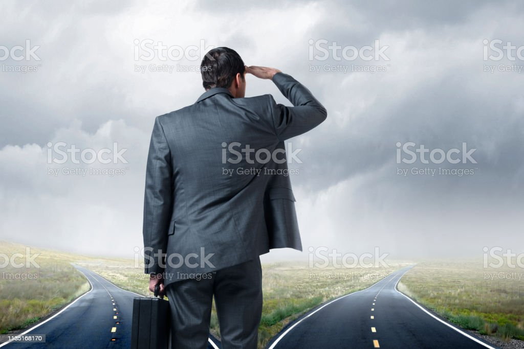 Businessman Standing At Fork In Road Looking Into The Distance stock photo