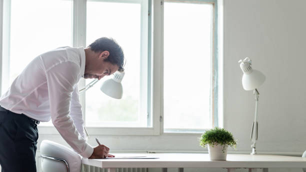 Businessman standing at his office desk leaning in to sign a contract stock photo