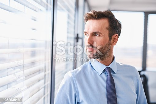Portrait of handsome businessman standing at office looking out the window