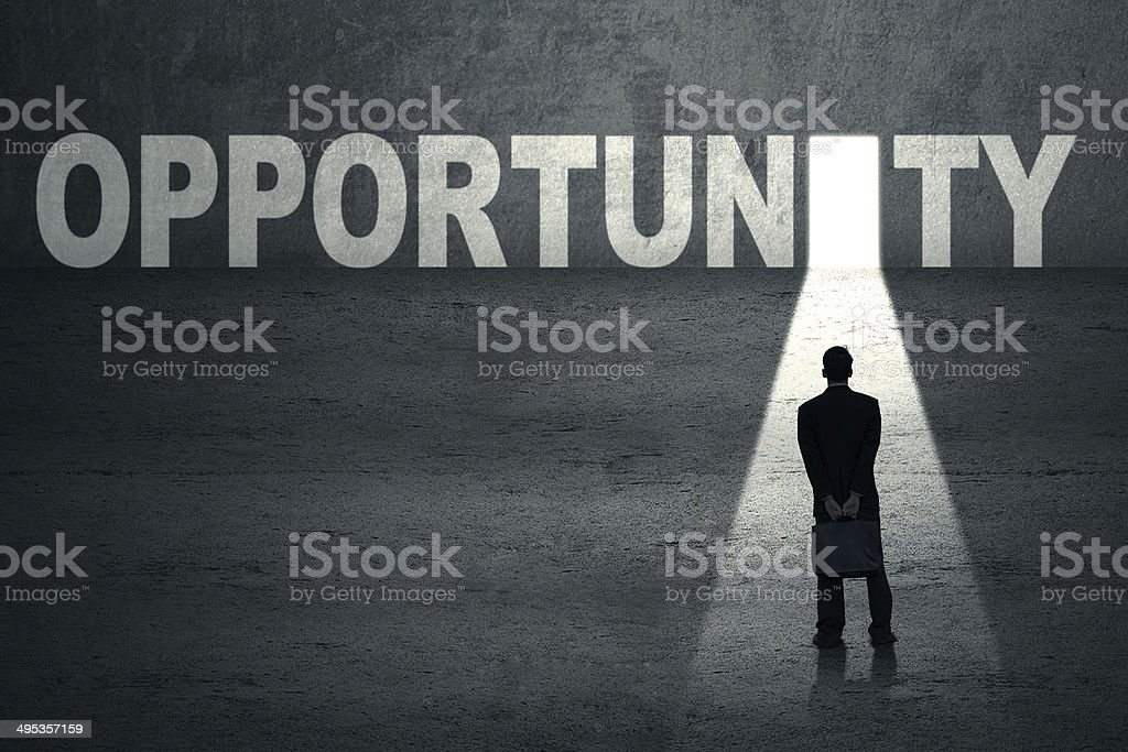 Businessman standing at opportunity door stock photo