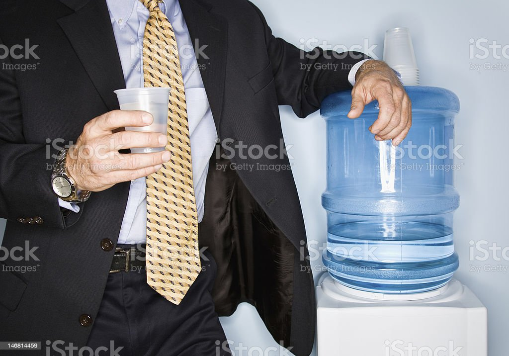 Businessman Standing at the Water Cooler stock photo