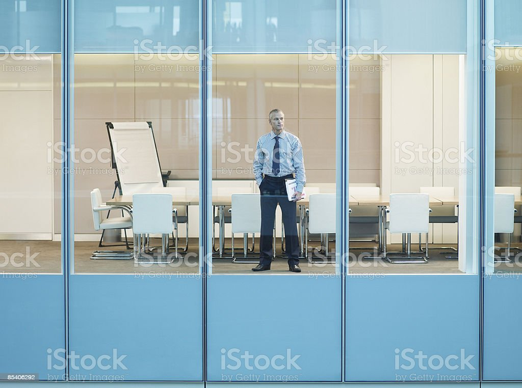 Businessman standing at window in conference room royalty-free stock photo
