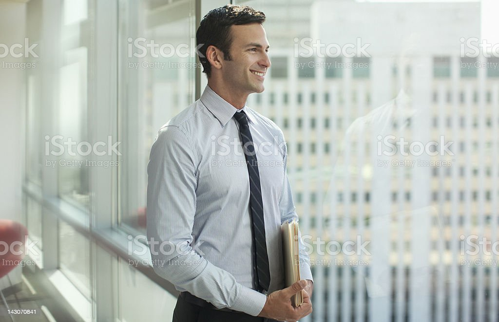 Businessman standing at window in office stock photo