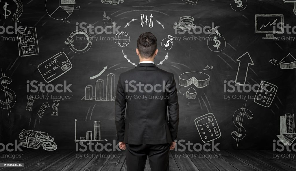 Businessman standing back to us looking at the blackboard with stock photo