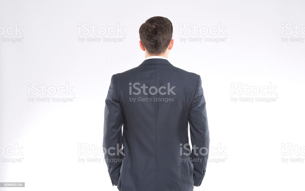 A businessman standing backwards stock photo