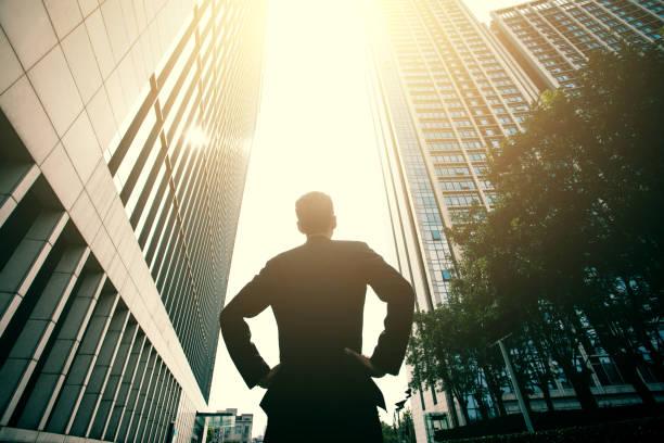 businessman standing between city buildings - guardare in su foto e immagini stock