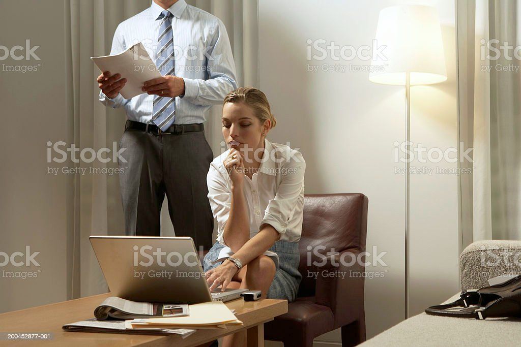 Businessman standing by businesswoman using laptop at coffee table royalty-free stock photo