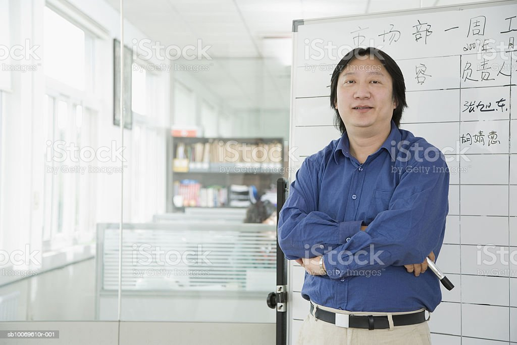 Businessman standing by flip chart, smiling, portrait royalty-free stock photo