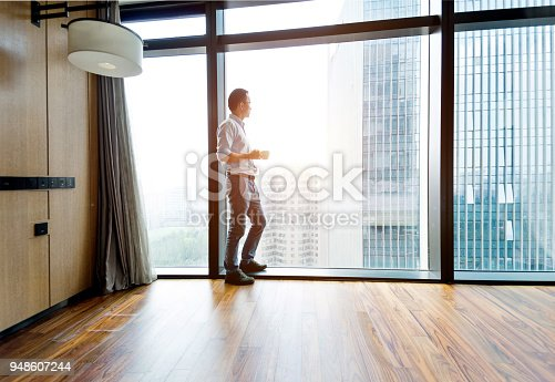 Businessman standing by the window and drinking coffee