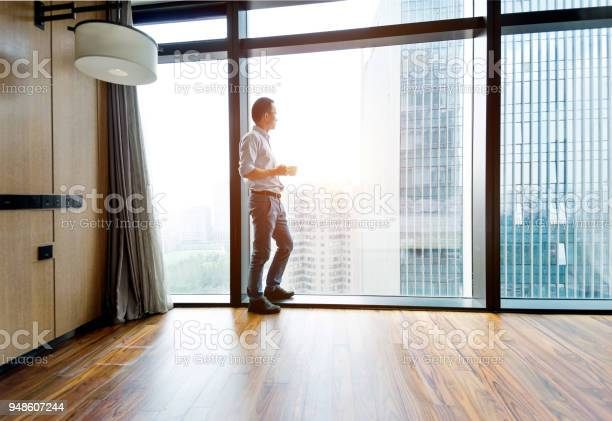 Businessman standing by the window and drinking coffee picture id948607244?b=1&k=6&m=948607244&s=612x612&h=gaiyupw2cadfhzyb9yvrwmnjsn5um2yhfmsrxyi3t w=
