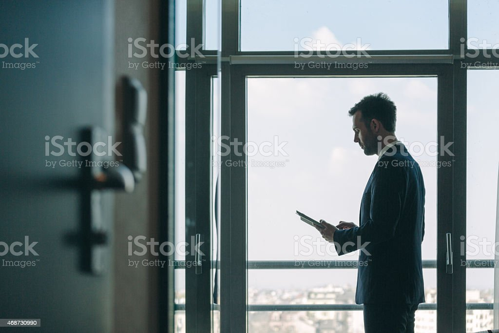 Businessman standing by the window and holding digital tablet Side view of businessman wearing suit standing by the window in an office and holding a digital tablet. Dark tone. 2015 Stock Photo