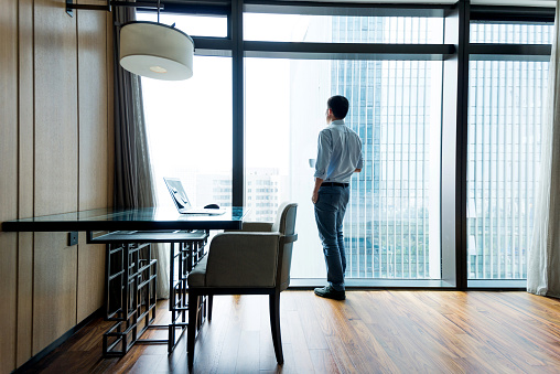 Businessman standing by the window to rest