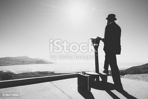 Businessman standing by viewpoint telescope, Business vision concept.