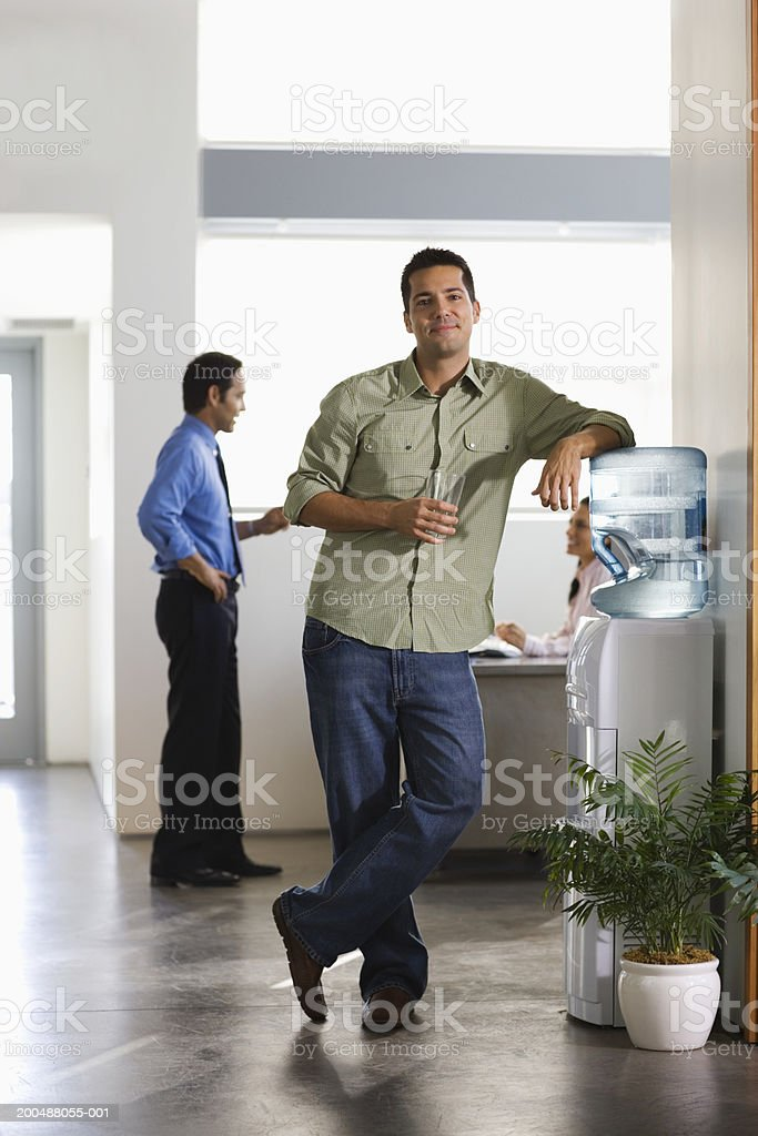 Businessman standing by water cooler in office stock photo