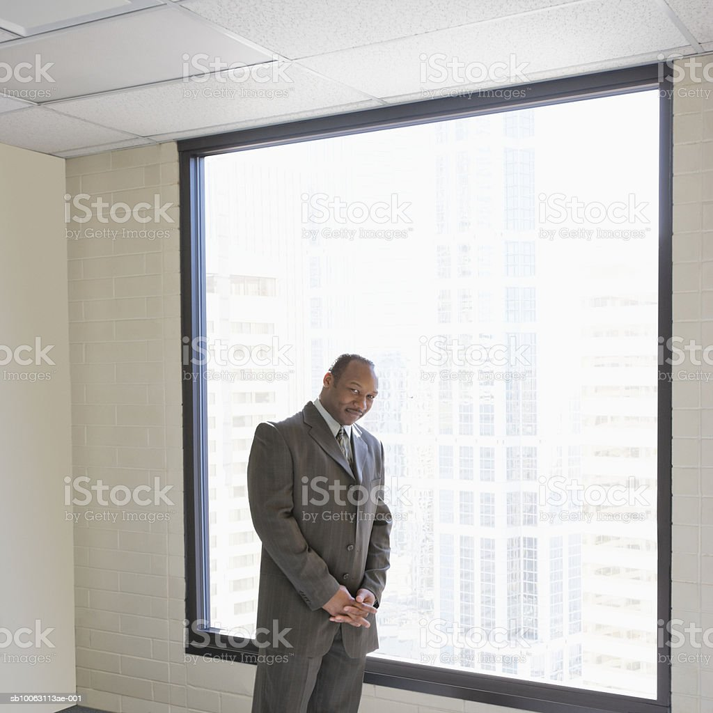 Businessman standing by window, smiling foto de stock libre de derechos