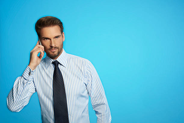 Businessman standing communicating on phone, isolated on blue background stock photo