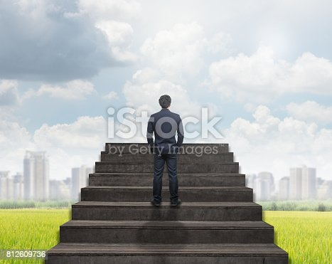 513121118istockphoto Businessman standing for walking up stairs over the  grass and cityscape under the cloud and sky background,Success business and Ambitions concept 812609736