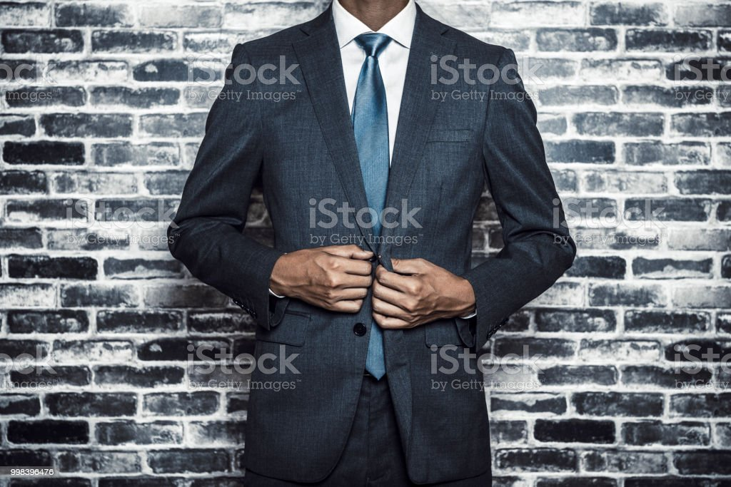 businessman standing front of a brick wall stock photo