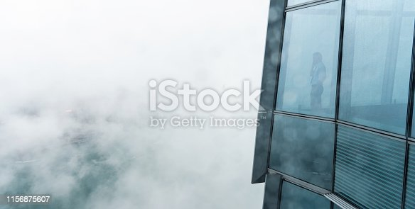 businessman standing in a skyscraper building viewing over the city.