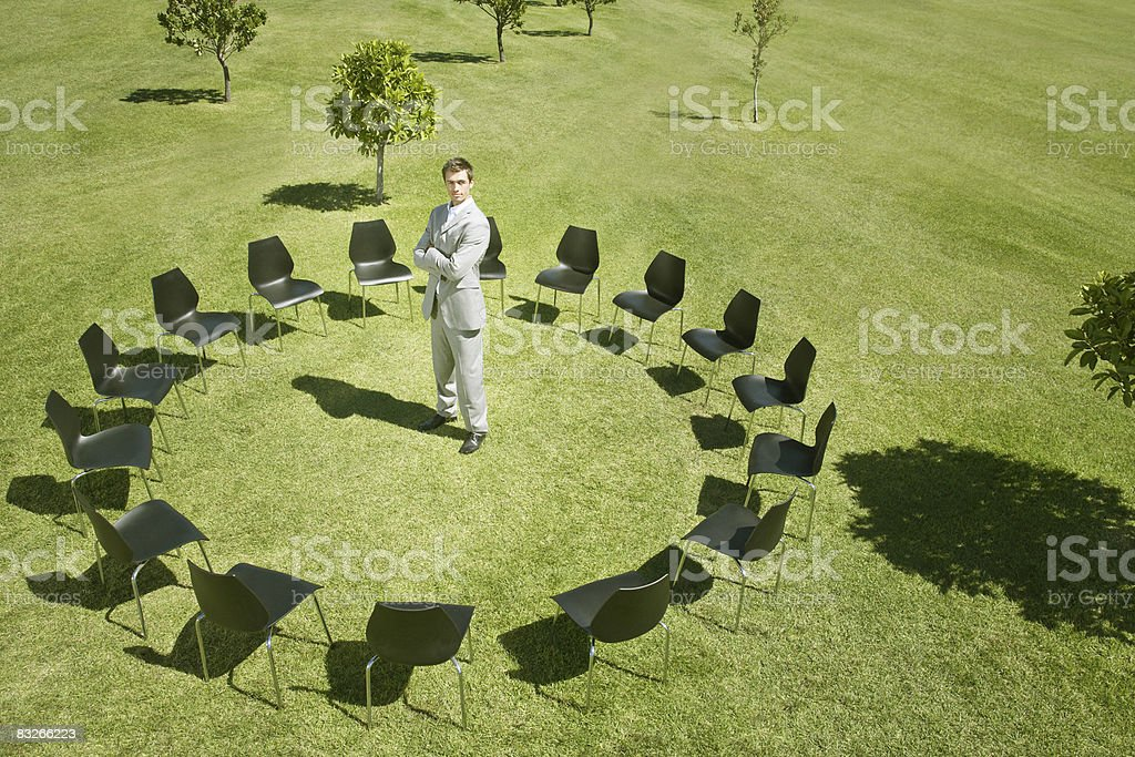 Businessman standing in circle of office chairs in field stock photo