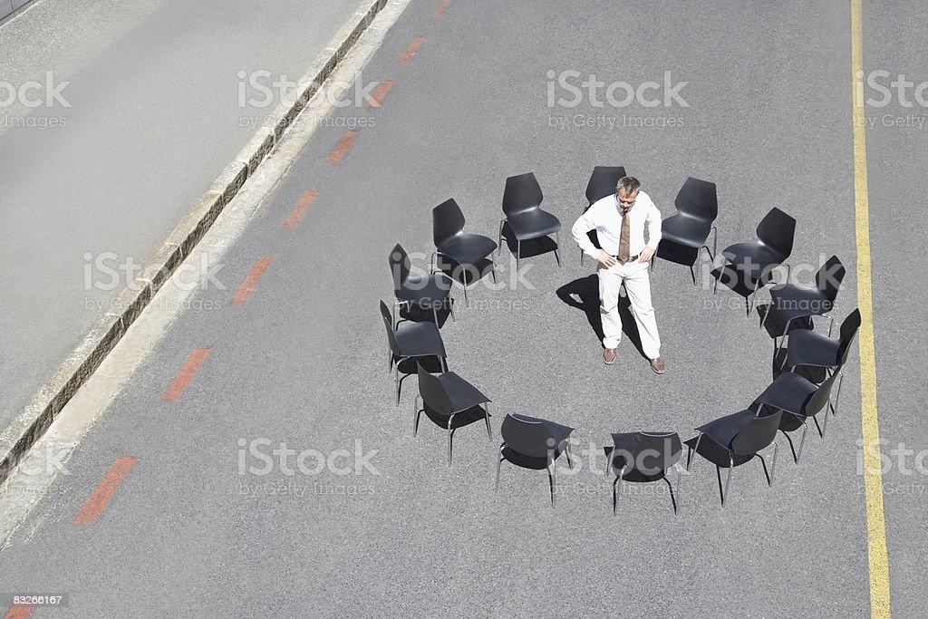 Biznesmen stojąc w kręgu biurowe krzesła w transport drogowy; zbiór zdjęć royalty-free