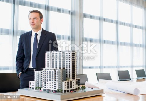 istock Businessman standing in conference room with model building 121330541