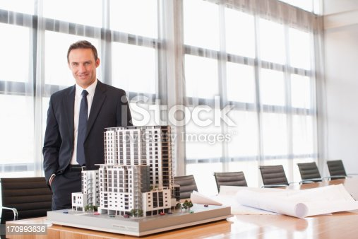 istock Businessman standing in conference room with model building 170993636