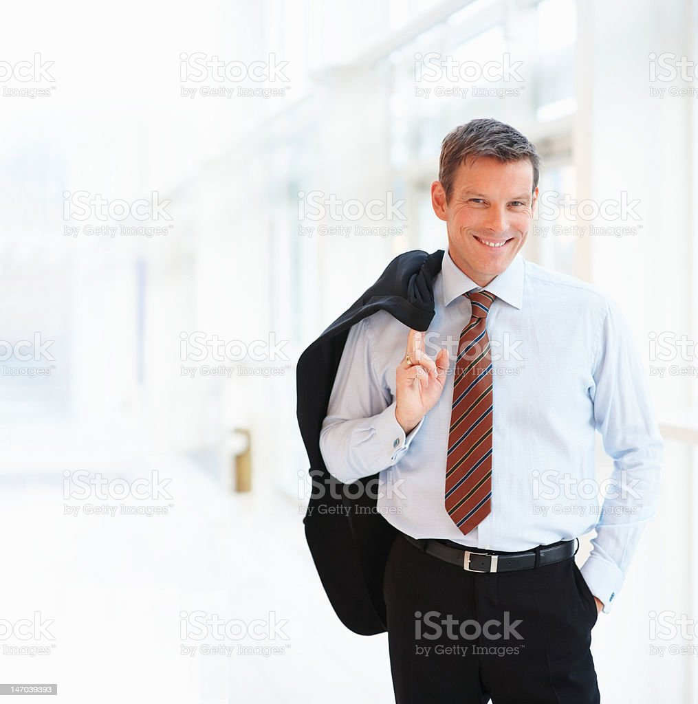 Businessman standing in corridor and smiling royalty-free stock photo