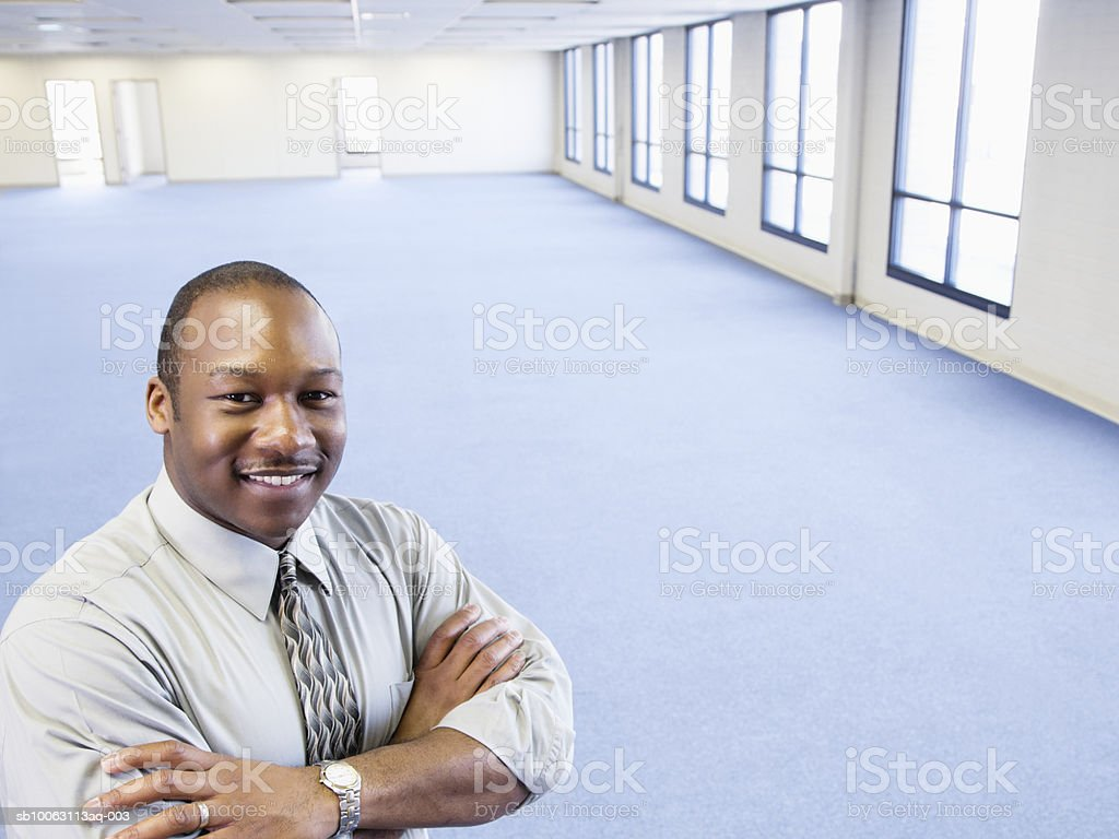 Businessman standing in empty office with arms crossed, smiling, portrait foto de stock royalty-free