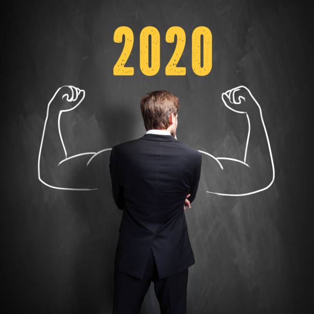 businessman standing in front of a blackboard with 2020 written on it stock photo
