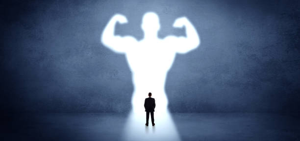 Businessman standing in front of a strong hero vision stock photo
