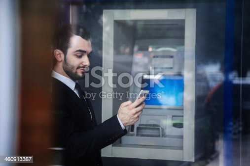 istock Businessman standing in front of an ATM 460913367