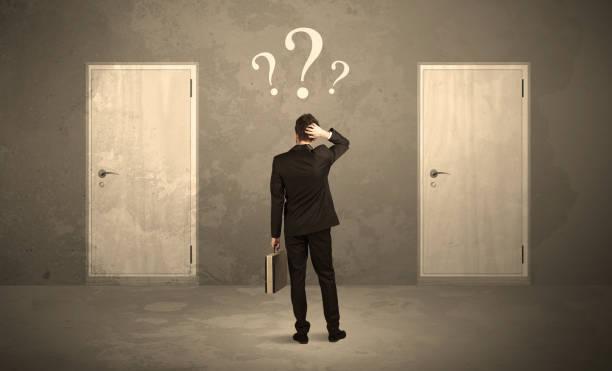 Businessman standing in front of doors stock photo