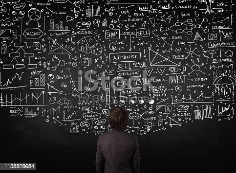 istock Businessman standing in front of drawn charts on a blackboard 1138828684