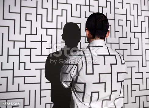 istock Businessman standing in front of labyrinth 467842358