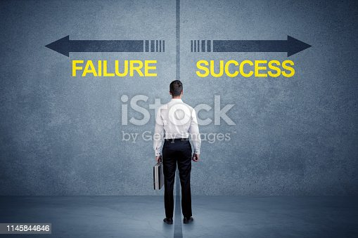 istock Businessman standing in front of success and failure arrow concept 1145844646