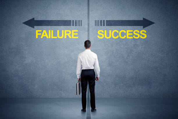 Businessman standing in front of success and failure arrow concept stock photo
