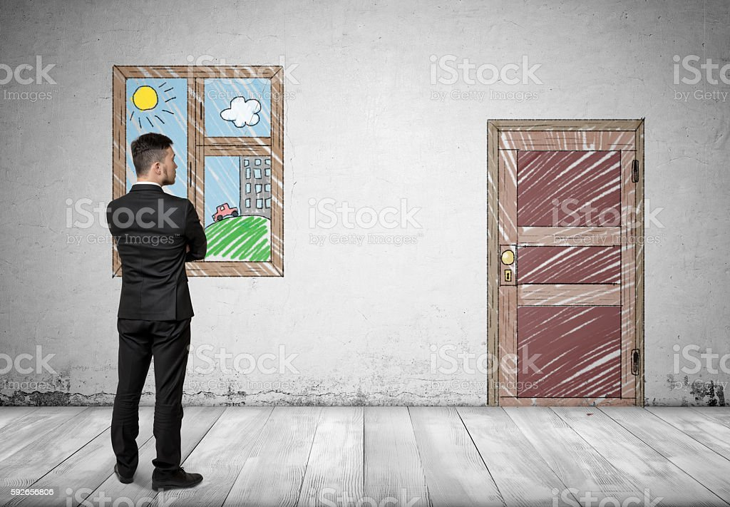 Businessman standing in front of the window looking at the stock photo