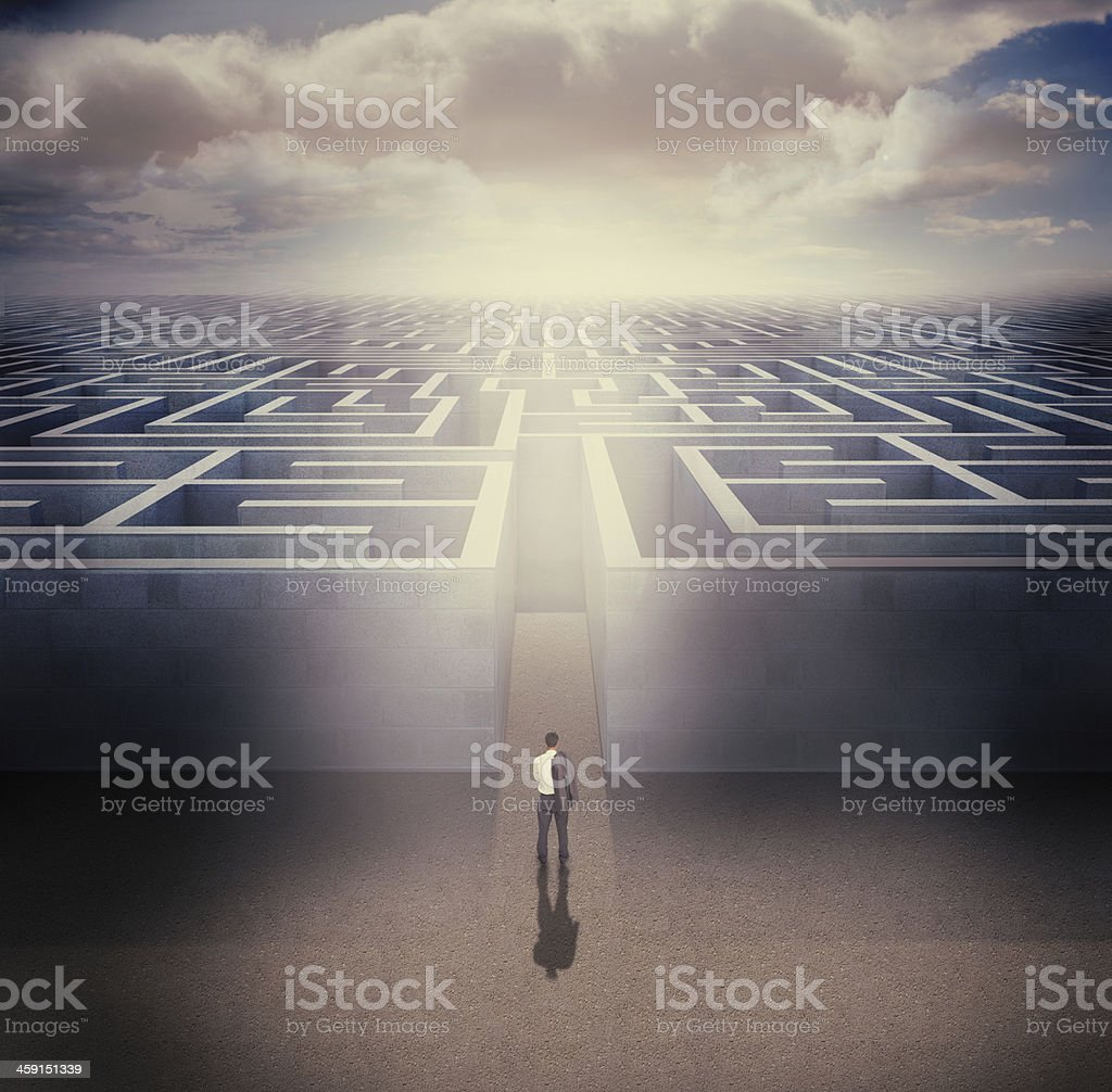 Businessman standing in front the entrance of a maze stock photo