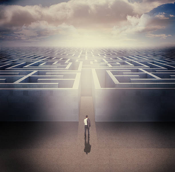 businessman standing in front the entrance of a maze - maze stock photos and pictures